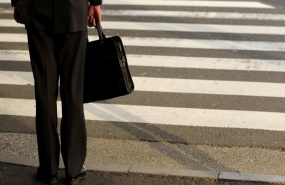 a-businessman-waits-to-cross-a-street-in-tokyo