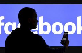 ep un hombre con un telefono movil delante de un cartel de facebook